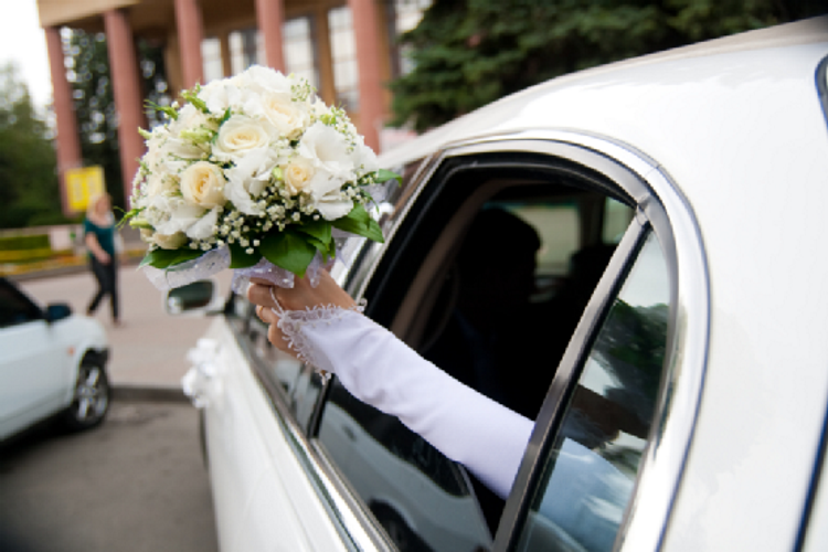 bride holding a bouquet in a white limo