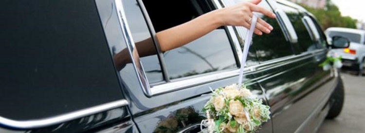 a hand stretching out of a limo window holding a bouquet