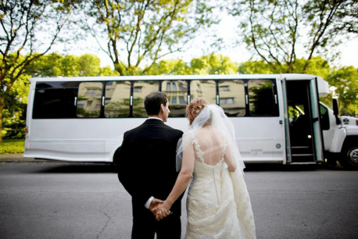 a bride and a groom in front of a white wedding bus